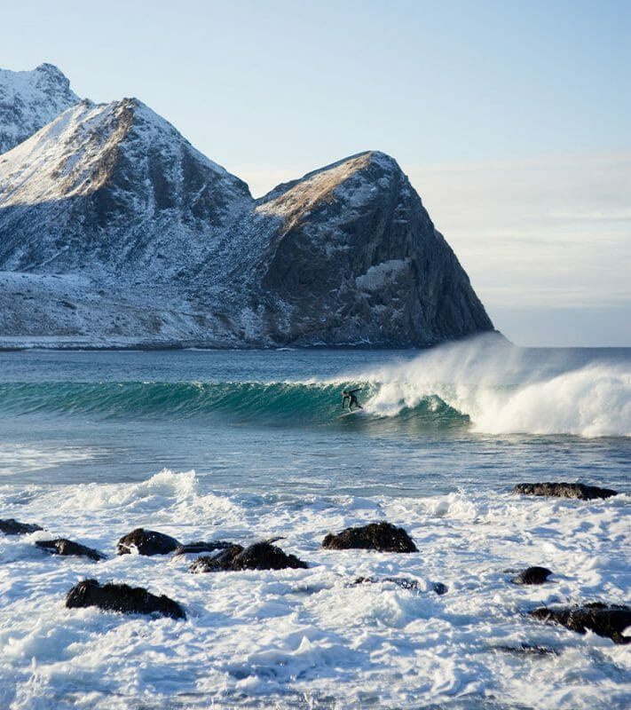 surfing on a snowy beach in Norway